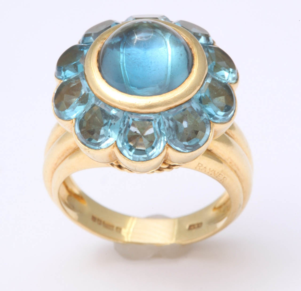 18Kt Yellow Gold ring set with Faceted Blue Topaz stones and a center Cabochon Blue Topaz  stone.  Signed Rayner on the outer shank and marked with British gold marks on the interior shank.