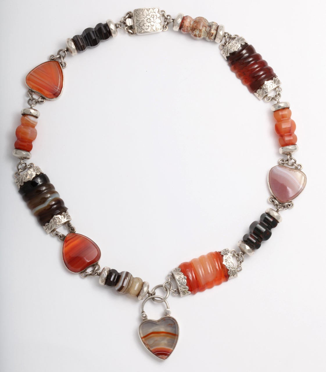 Carved and ridged banded agate and carnelian is set in engraved sterling then linked and interspersed with agate hearts.  The original clasp on this necklace is intact as is the floral engraved padlock with the same engraving that will sit near your