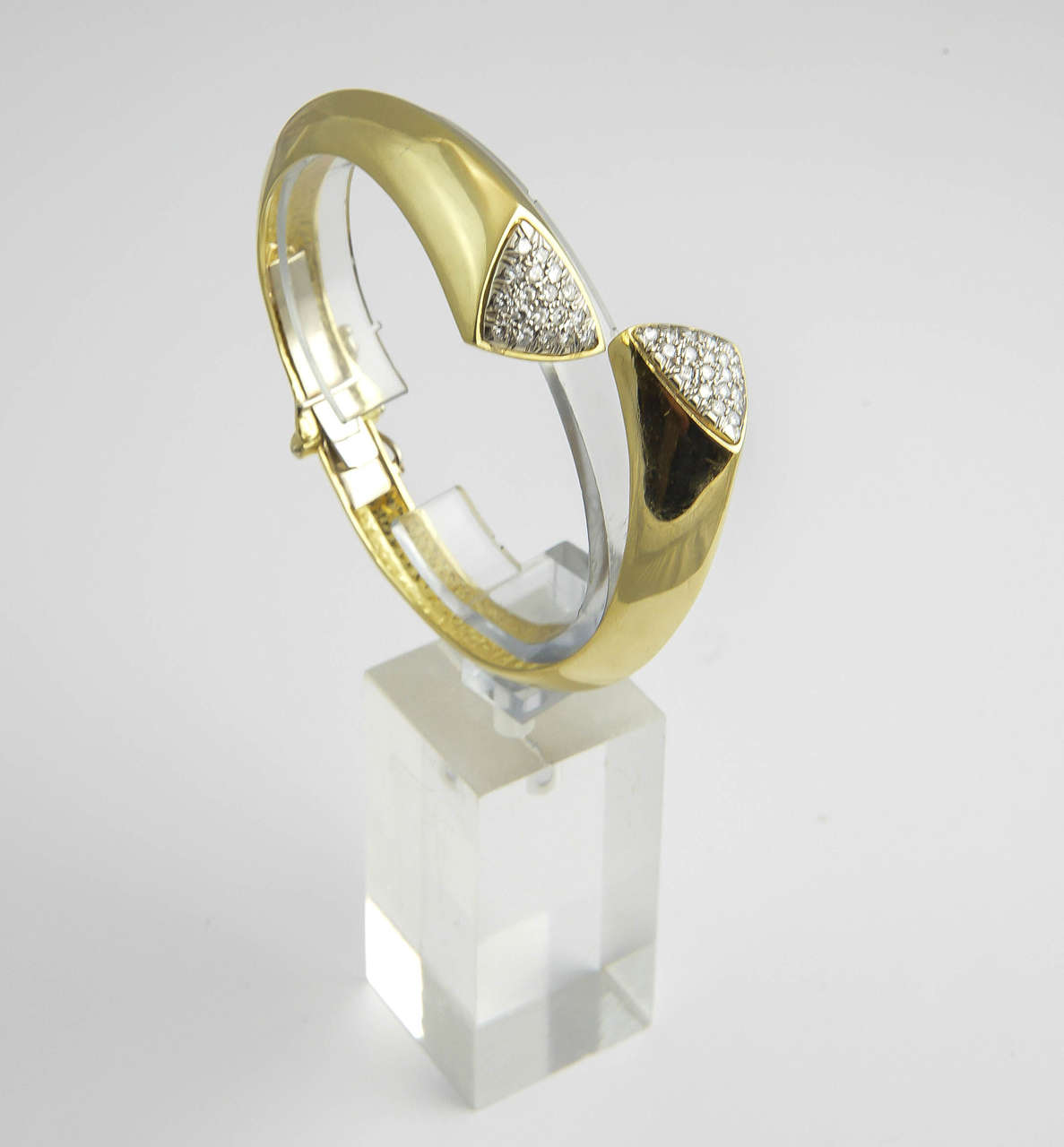 Geometric 18k gold hinged bangle bracelet with pave diamond triangles.