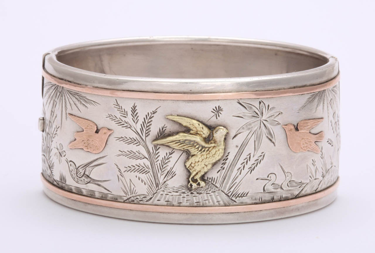 With its pronounced rose gold borders and birds n flight the bracelet you see here is even stronger in design in person. It has movement in the engraved drawing of grasses and birds as if a strong breeze was present. It has the calm of the water