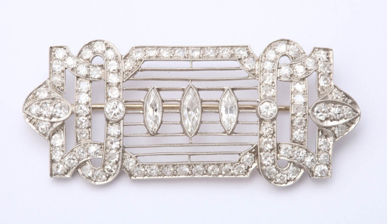Like a musical notation, three marquise diamonds rest upon horizontal platinum bars. The surround is looped, and arched, encrusted with diamonds passing over and under ovals. There is a lot of geometry, all delicate,  forming an elegant,