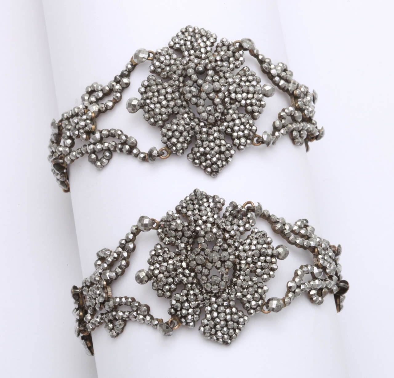 Two are better than one when you find a rare pair of cut steel bracelets made of tightly clustered cut steel rivets that form flowers and bows along the seven inch length these Georgian bracelets. The rivets are so small that they could be poppy