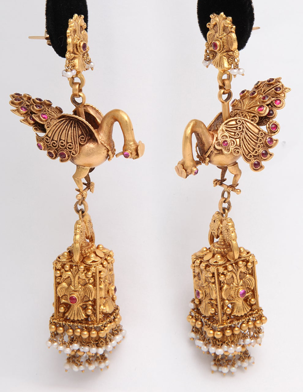A pair of earrings composed of 18kt yellow gold peacocks with bezel set cabochon ruby eyes and feathers. The peacocks suspend 18kt yellow gold  cages. The cages showcase four bird plaques. The cages have 18kt yellow gold and pearl fringe at the