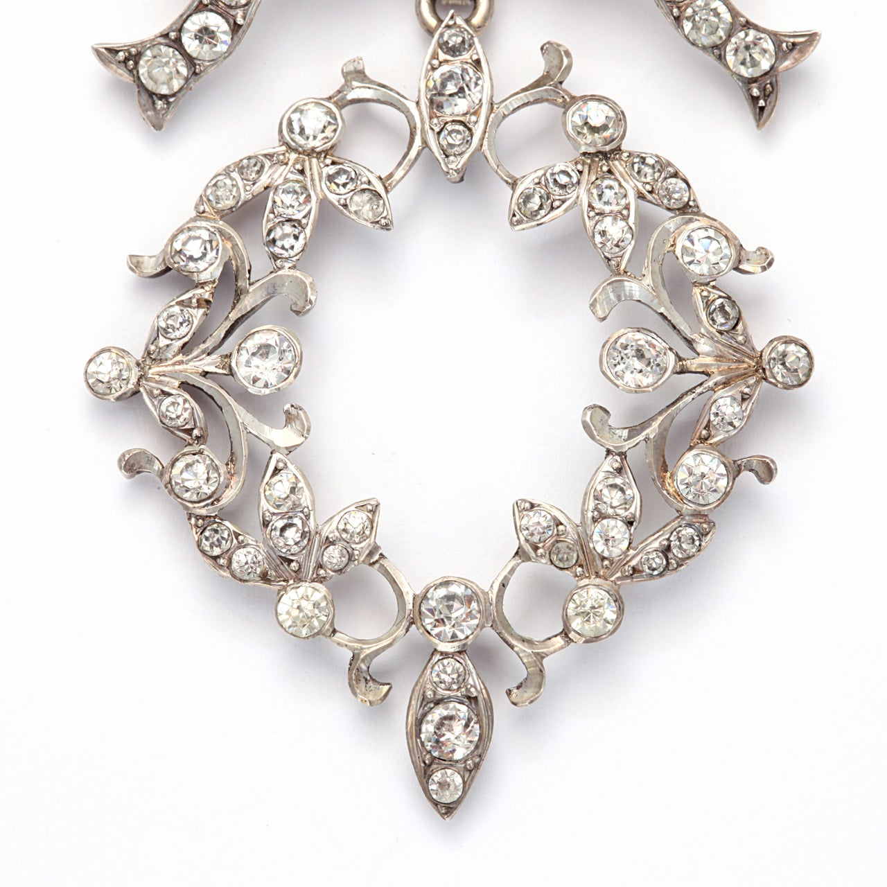 Graceful and unusual, with a bow as a reminder of affection, this silver and paste pendant was made in France in the Art Nouveau period when curves and swirls and garlands dressed architecture and ladies. The paste stones are a variety of sizes, a