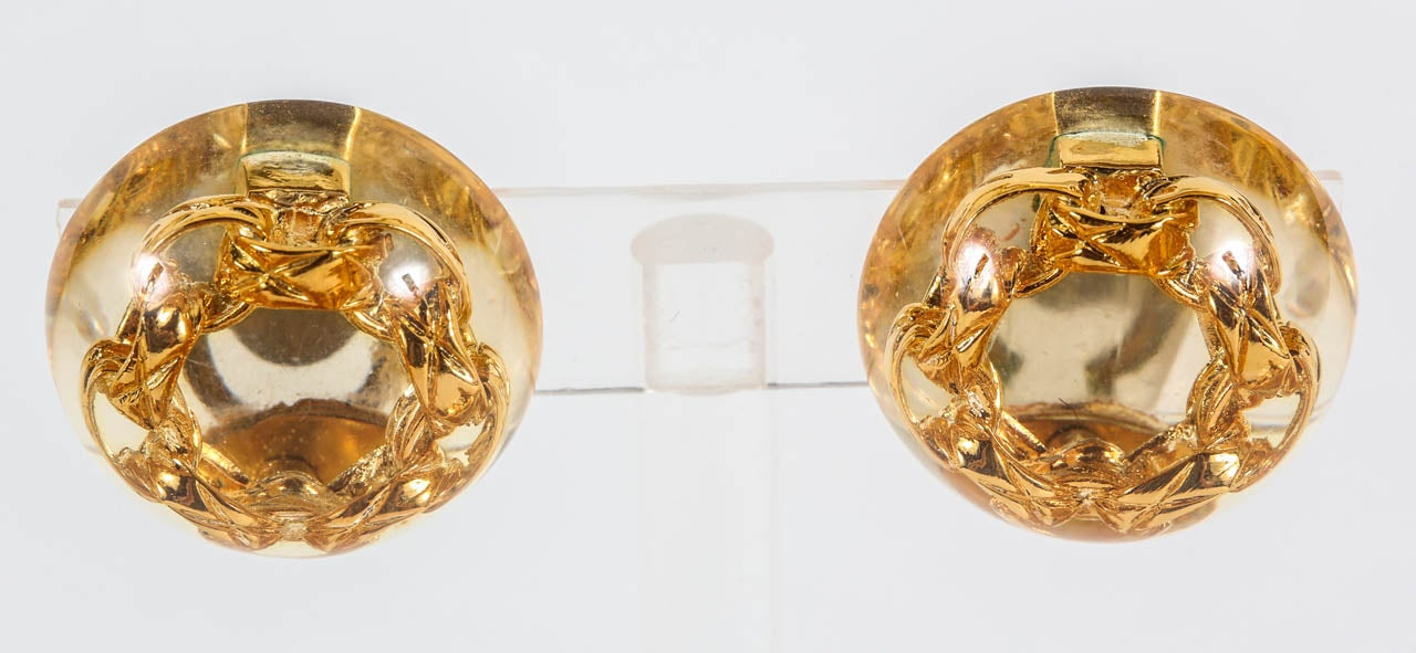 "An elegant pair of ear clips by Chanel, featuring their signature quilted gilt metal chain in cast resin. Marked on the back with the ""Chanel Made in France"" oval cartouche indicating that this is from collection 25, designed by then head designer,"