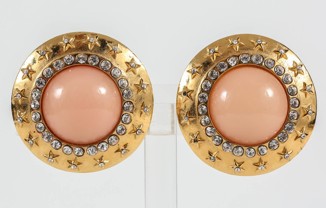 A chic pair of ear clips with a faux coral glass center surrounded by rhinestones and a frame of raised rhinestone-set stars. Marked on the back with just the Chanel name, indicating these are earlier Chanel, most likely from the late 50s/early 60s.