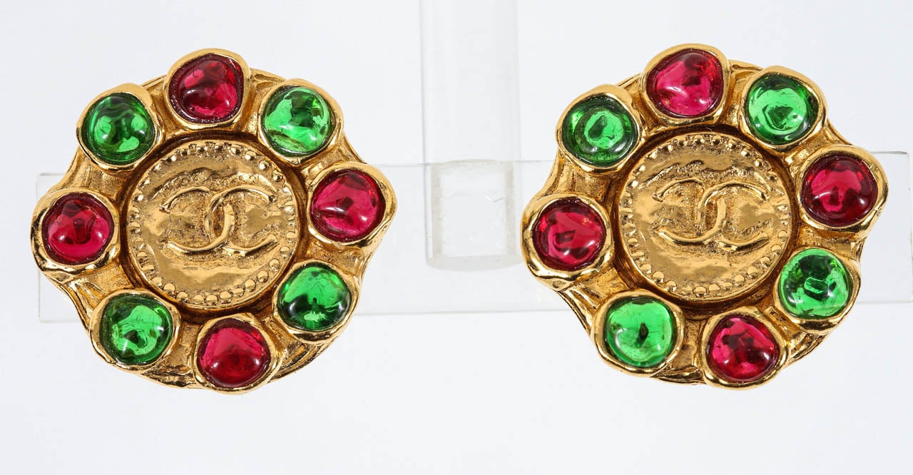 "A classic pair of Chanel ear clips with a beaded edge center coin featuring the interlocked C logo, framed by irregular red & green poured glass stones. Marked on the backs of the ear clips with the ""Chanel"" ""Made in France"" round cartouche (see"