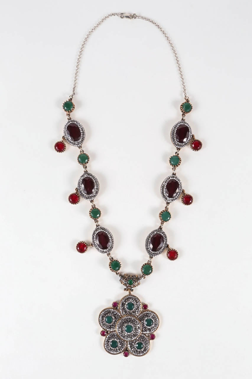 A 20th century homage to Mogul jewelry, this beautiful gold washed sterling silver necklace & earring set is set with sparking rhinestones and faceted paste stones. Stamped
