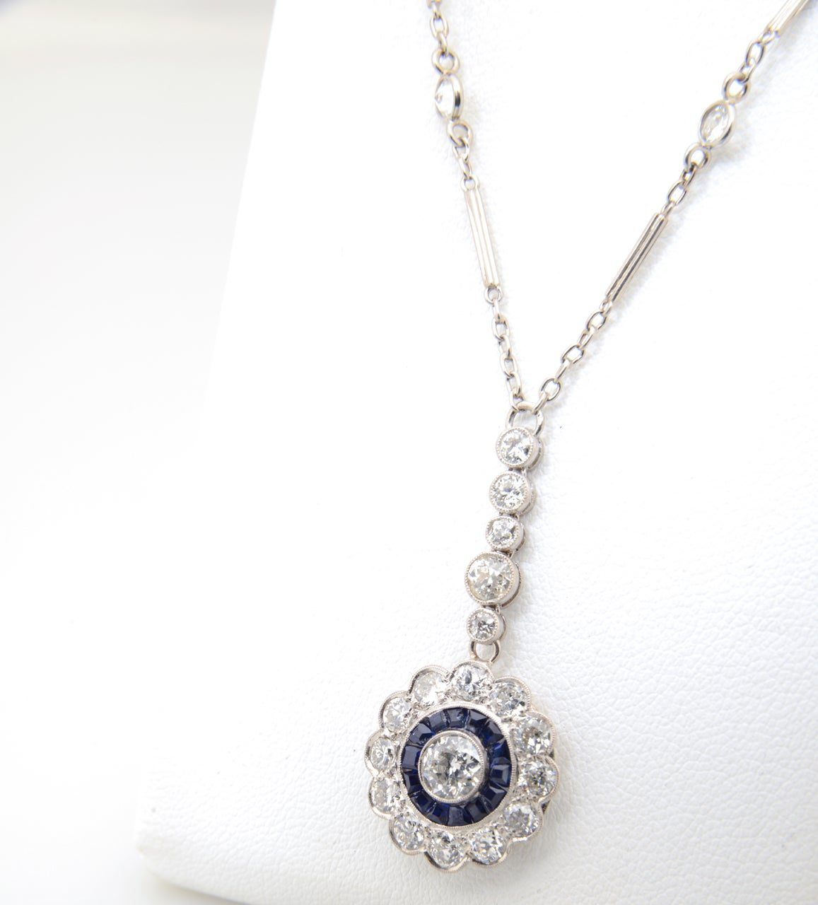 Finely made Art Deco diamond flower with a channel set sapphire ring around a .50 carat European cut diamond (approximate weight). The diamonds in the petals and drop are approximately another 1.5 carats.   The pendant measures  1 1/2