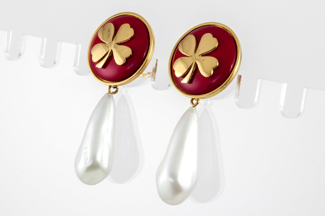 """A pretty pair of ear clips by Chanel featuring a gilt metal clover set on red resin with a glass pearl teardrop dangling from it. Stamped on the back """"Chanel""""."""