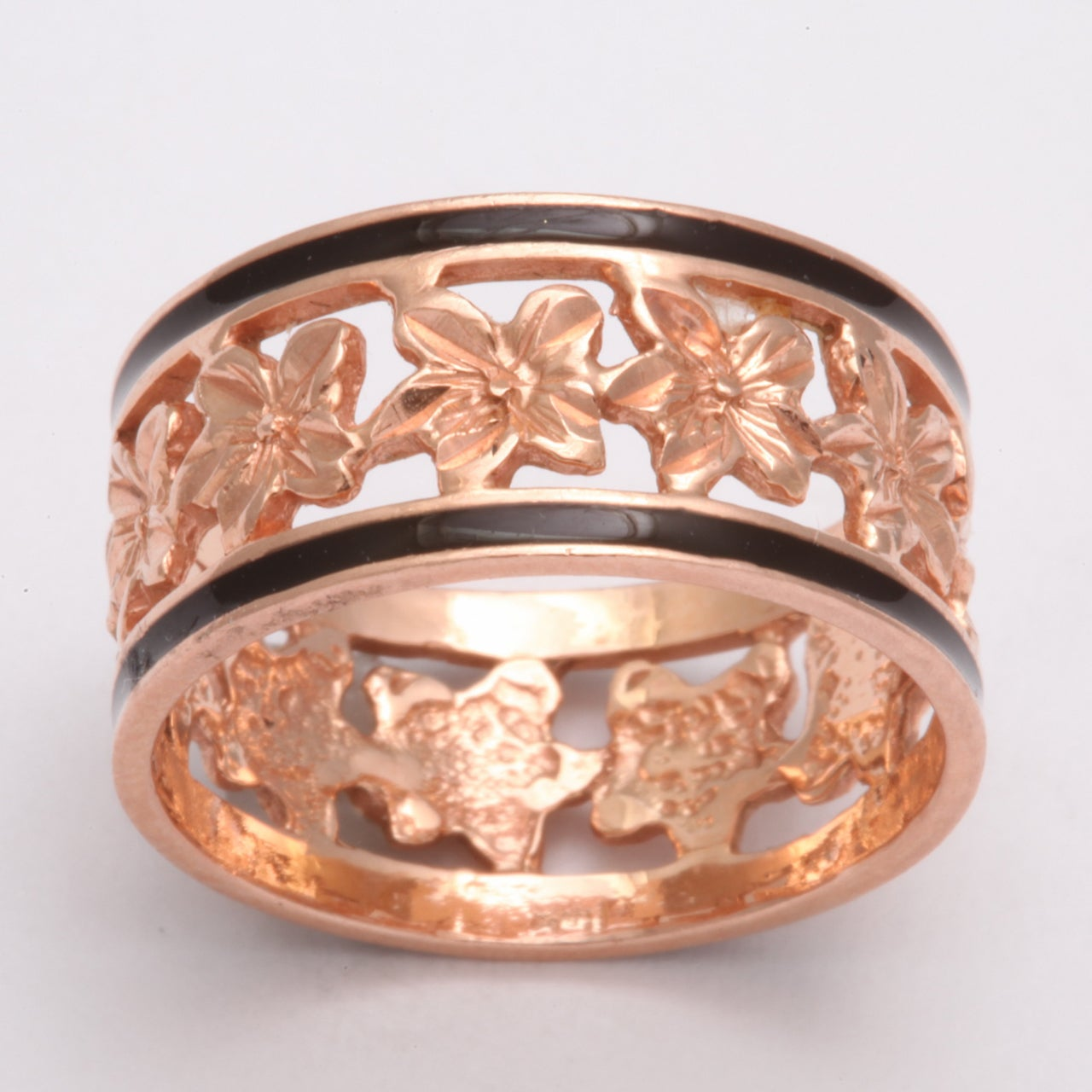 A band ring made in the United States in 14 Kt gold wraps ivy leaves around the finger. Ivy clings and intertwines in endless attachment which makes this a meaningful ring for lovers. The borders are emboldened with black enamel giving definition to