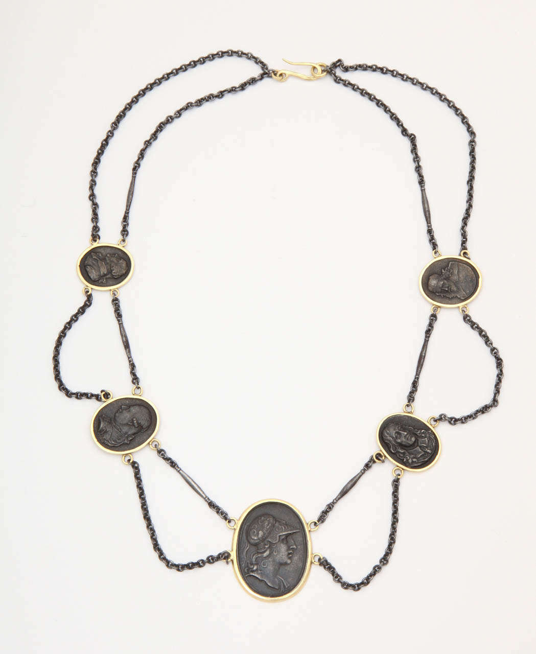 The fine, rare pairing of Berlin Iron and gold combine in this extraordinary garlanded necklace. Five neo -classical  iron portraits of historic figures are framed and set in gold. The portraits are crisp and detailed. Iron chain forms garlands