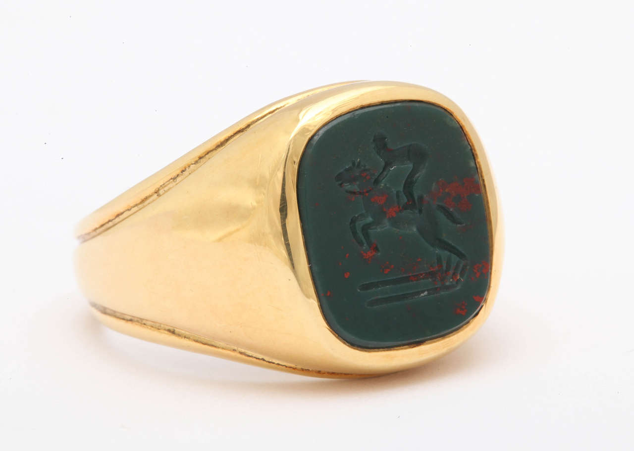 The intaglio was carved in Idar-Oberstein, Germany from Scottish bloodstone. It depicts a horse and rider jumping over a fence. This is a great ring for the steeple chaser or fox hunter or any equestrian sport enthusiast. The ring is now a size 9.5