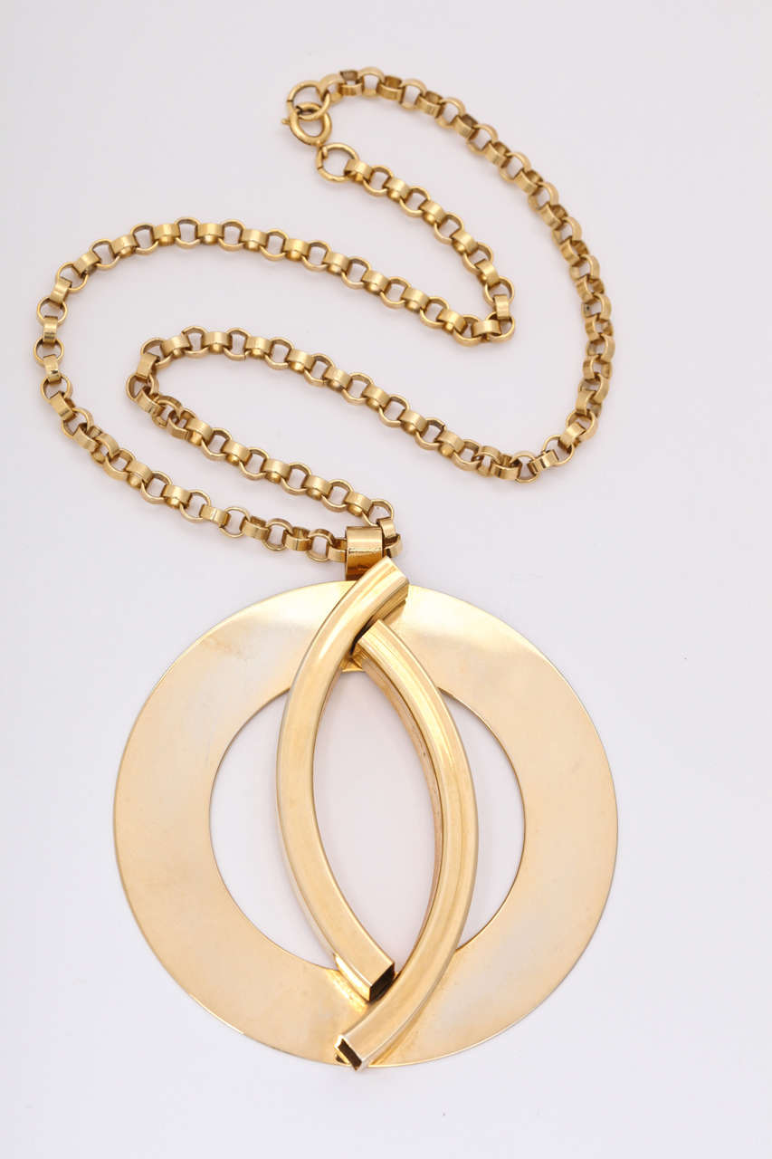 Large flat circle medallion necklace with two raised arch pieces on a chunky chain. Chain is 20