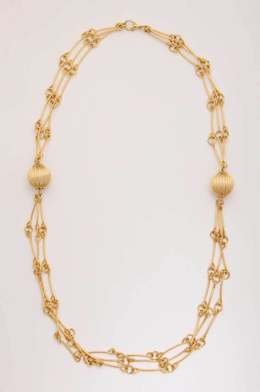 Triple strand link necklace with two balls.