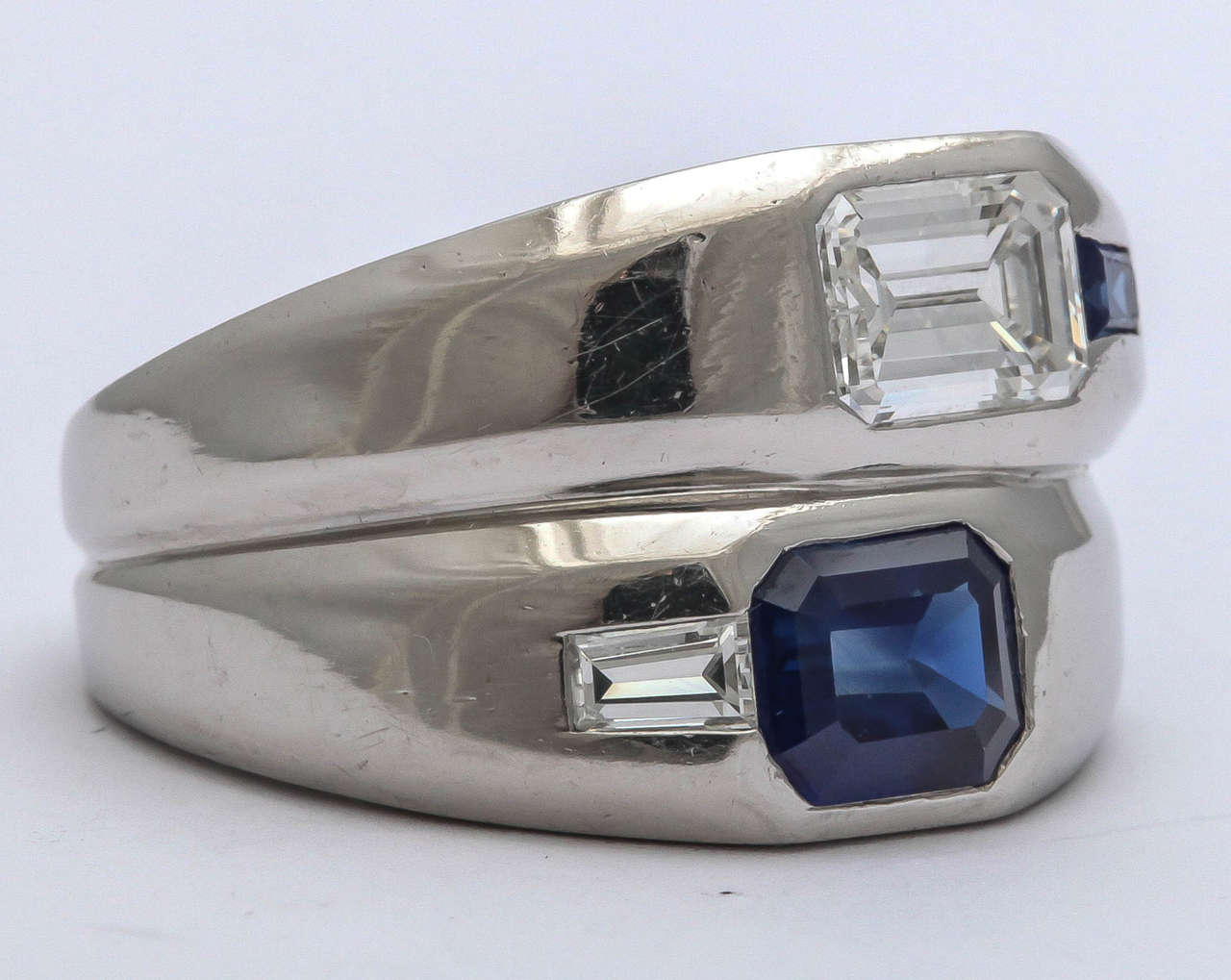 Fabulous double wide Platinum band with asymmetric opposition of an approximately 1.10ct Emerald cut Diamond and a Sapphire Baguette  and an approximately 1.30ct Emerald cut Blue Sapphire with a 15pt Diamond Baguette.  Perfect for a man or as a