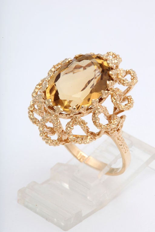 Striking 1960s citrine ring featuring a large facetted oval citrine in a hand made stylized 14k yellow gold mounting.  The open gold swirls create a floral design.  Size 10 - It can be sized.