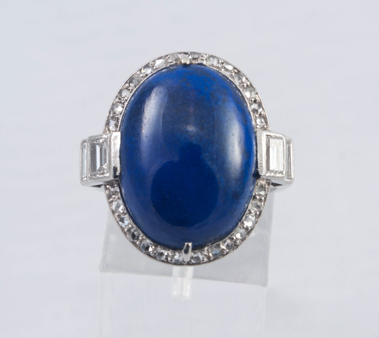 Cabouchon cut Lapis Lazuli ring surrounded by mixed cut small Diamonds and Baguettes set in Platinum ( tested ). It is engraved under the bezel with a fine reeded shank