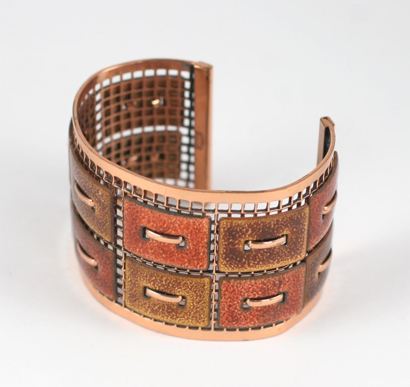 Copper grid cuff with rectangular copper and enamel pieces attached to grid.
