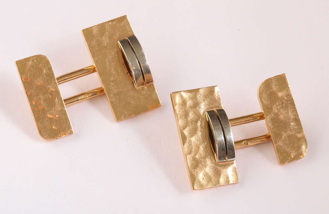 The martele base in yellow gold has applied to it a convex double bar in white gold attached by an oval ring to the small side with martele surface and square corners alternating with round corners.  Hallmarked for 18 kt gold with eagle's head/