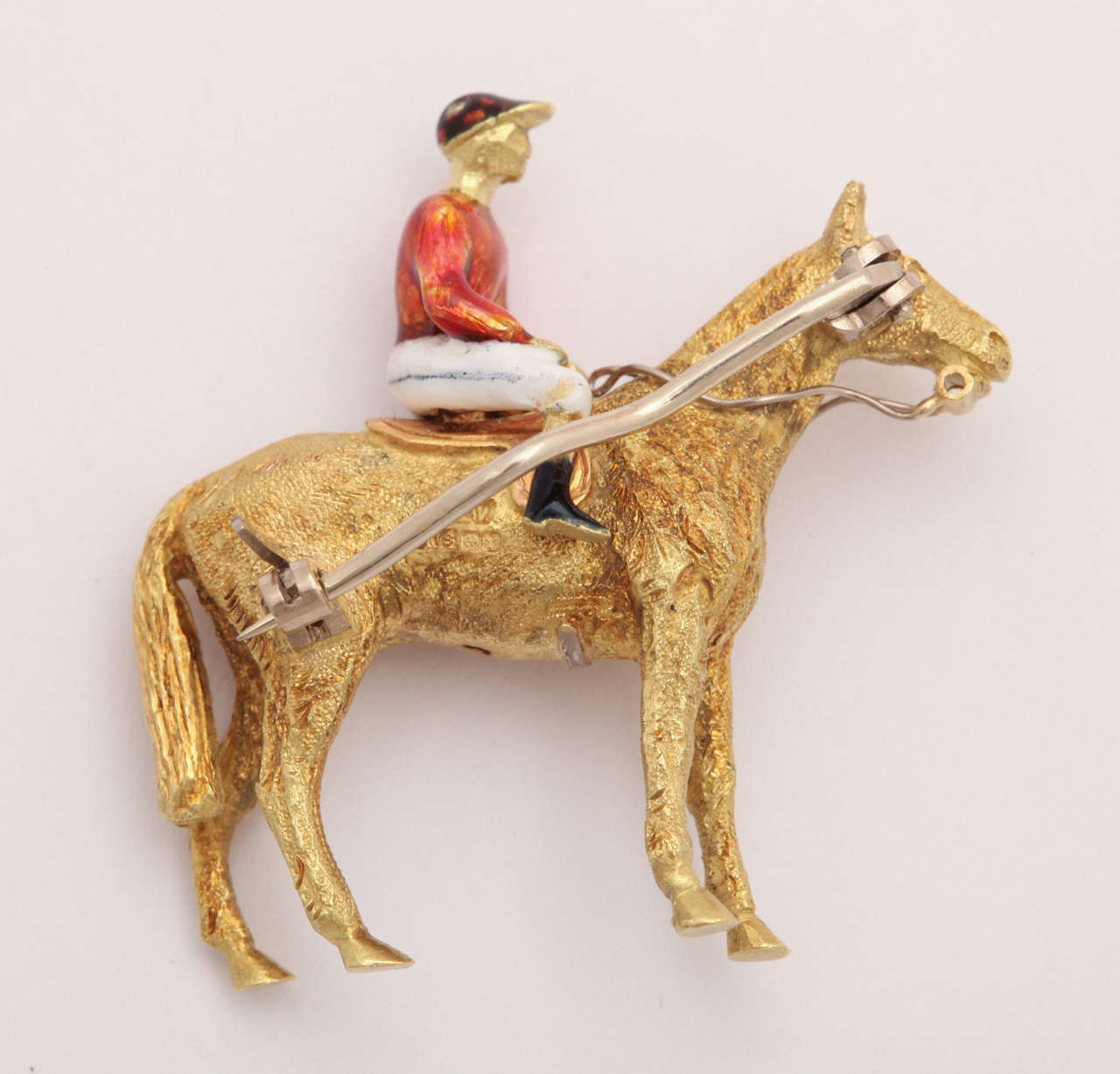 From Great Britain and one of the finest enamel workers in London comes a textured 18 kt and enamel horse and jockey pin. It is a remarkably crafted small sculpture that is three dimensional and stands on all fours. The form of the animal and the