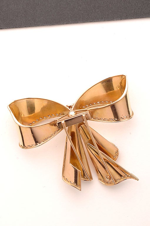 Retro fourteen karat gold bow pin with diamonds. Gold beautifully formed to give the effect of draped fabric.