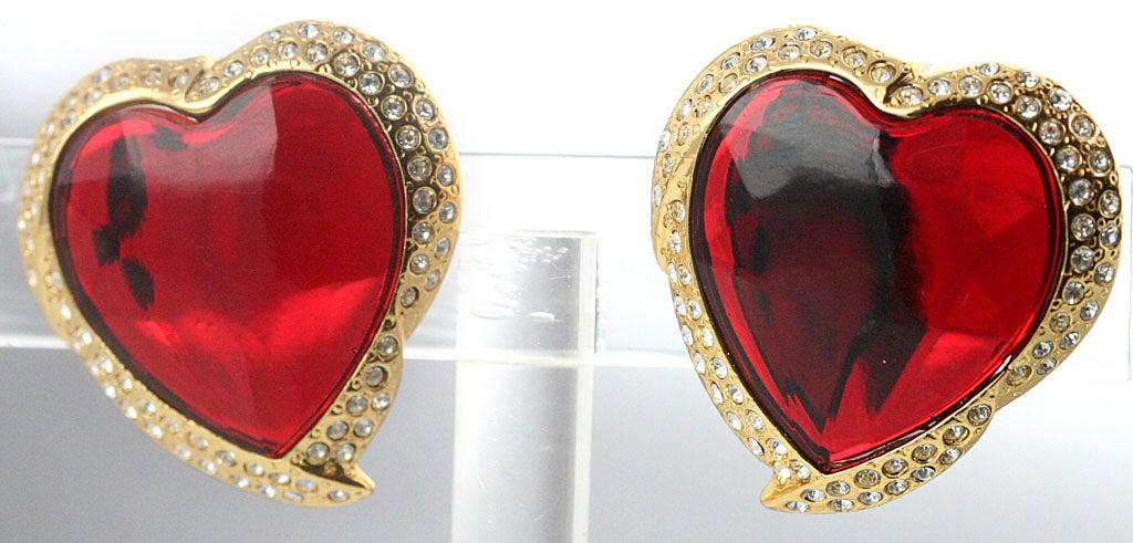A whimsical pair of heart shaped ear clips by YSL with a sparkling red heart center set in gold plated metal inset with rhinestones.