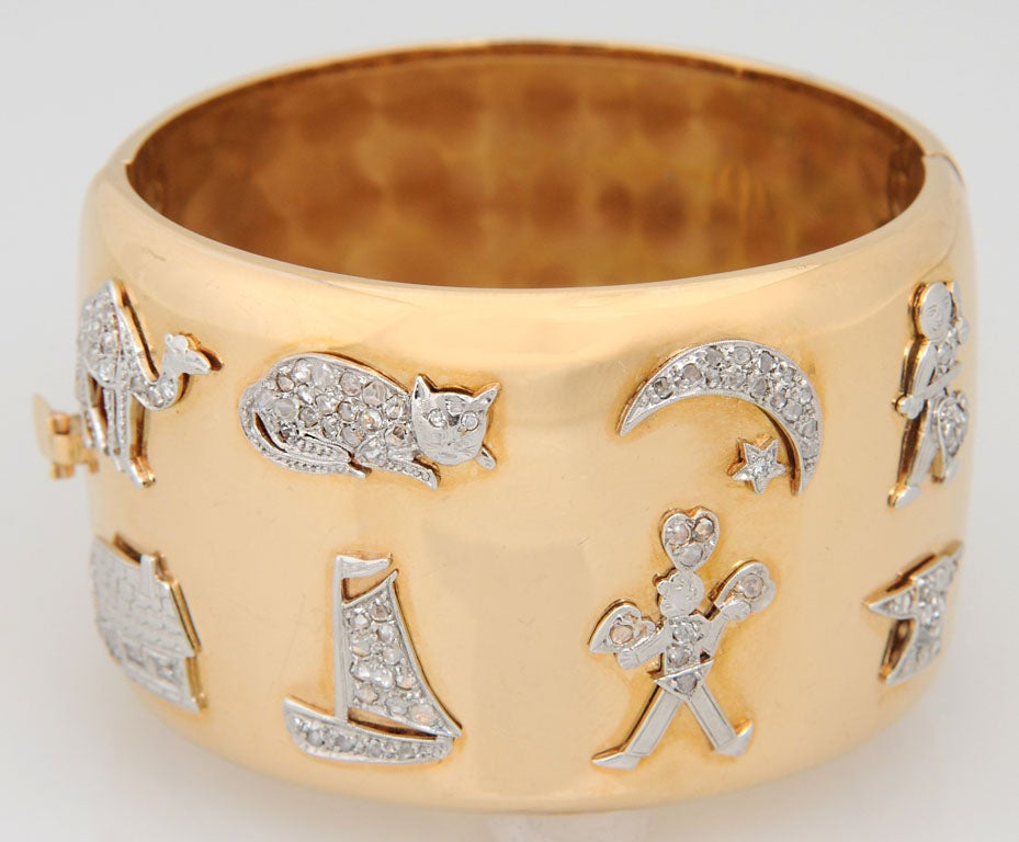 This is a wonderful marriage of 8 Deco platinum and diamond charms: Camel, Cat, Moon & Star, Musician, House, Boat, Anvil, and a Man holding Hearts (possibly a juggler).  These platinum charms were put into this 18k yellow gold bangle in the 40's.