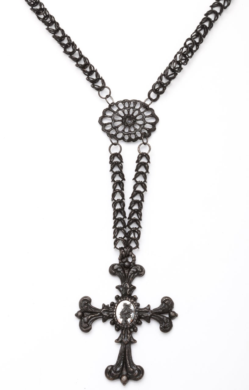 The Georgian Berlin Iron Chain, composed of intricate interlocking links. drops nine inches from the clasp top section and 14 inches over all to the bottom of the ornamental cross, falling to the top of the breast. This top section is separated from