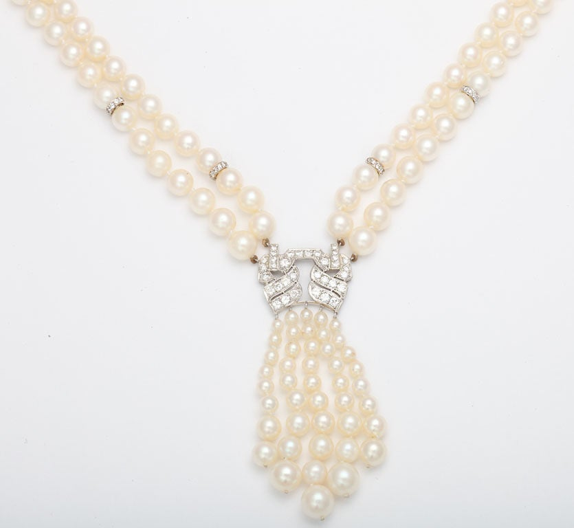 Double strand Cultured Pearl Necklace interspersed with 8 Diamond set Rondels, and centered with a Platinum & Diamond Element & terminating with a graduated Pearl Tassel.