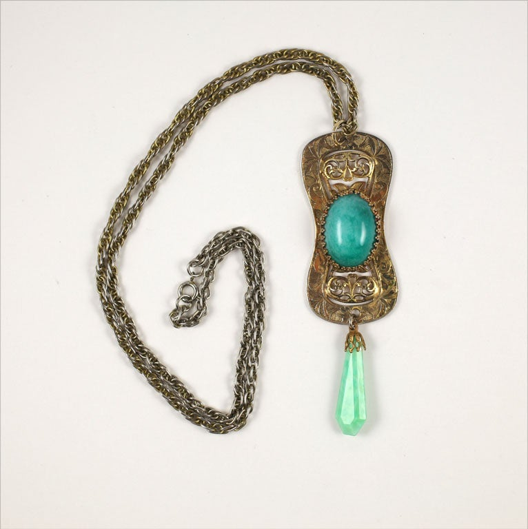 Goldtone filigree pendant with prong set faux jade cabochon and drop suspended from a chain.