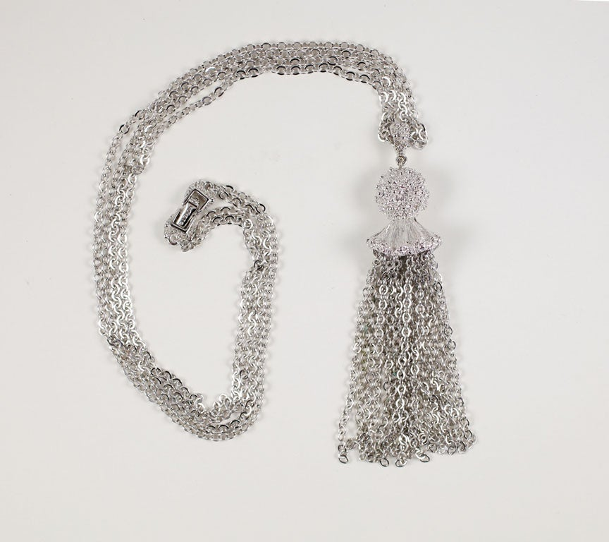 Double chain silvertone necklace with a textured cap multi chain tassel.