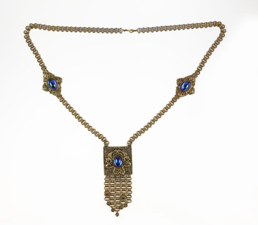Goldtone necklace with three blue iridescent cabochons, a decorative chain, and a double dragon embellished filigree pendant with five art glass beads .