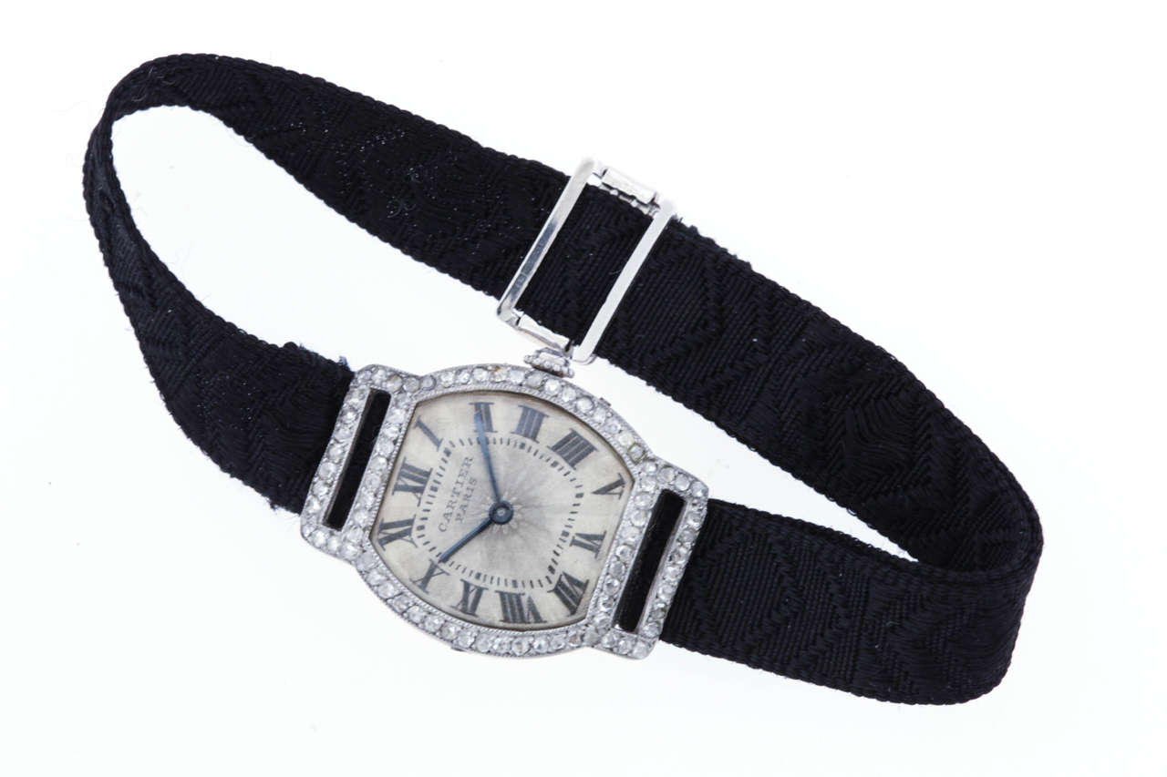 Cartier platinum, diamond  and 18K yellow gold Art Deco Tortue wristwatch, circa 1925. An extremely rare wristwatch with a grosgrain ribbon bracelet. The 20mm x 26mm tonneau case has a  yellow gold back with 4 screws in the platinum band. The bezel,