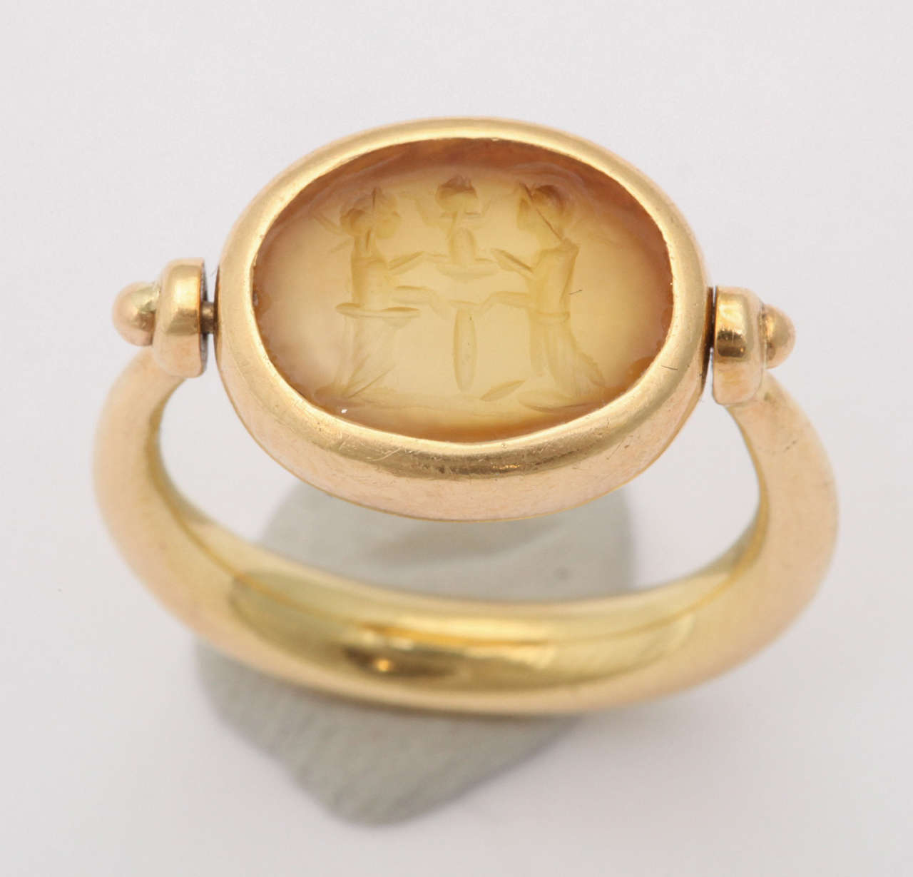 Splendid Pinky  Ring set in Oval 18kt Yellow Gold swivel mounting. Lovely Intaglio of two opposing Gods & a central Figure. Inscribed Roma  2 sec d C & 750 & control numbers.