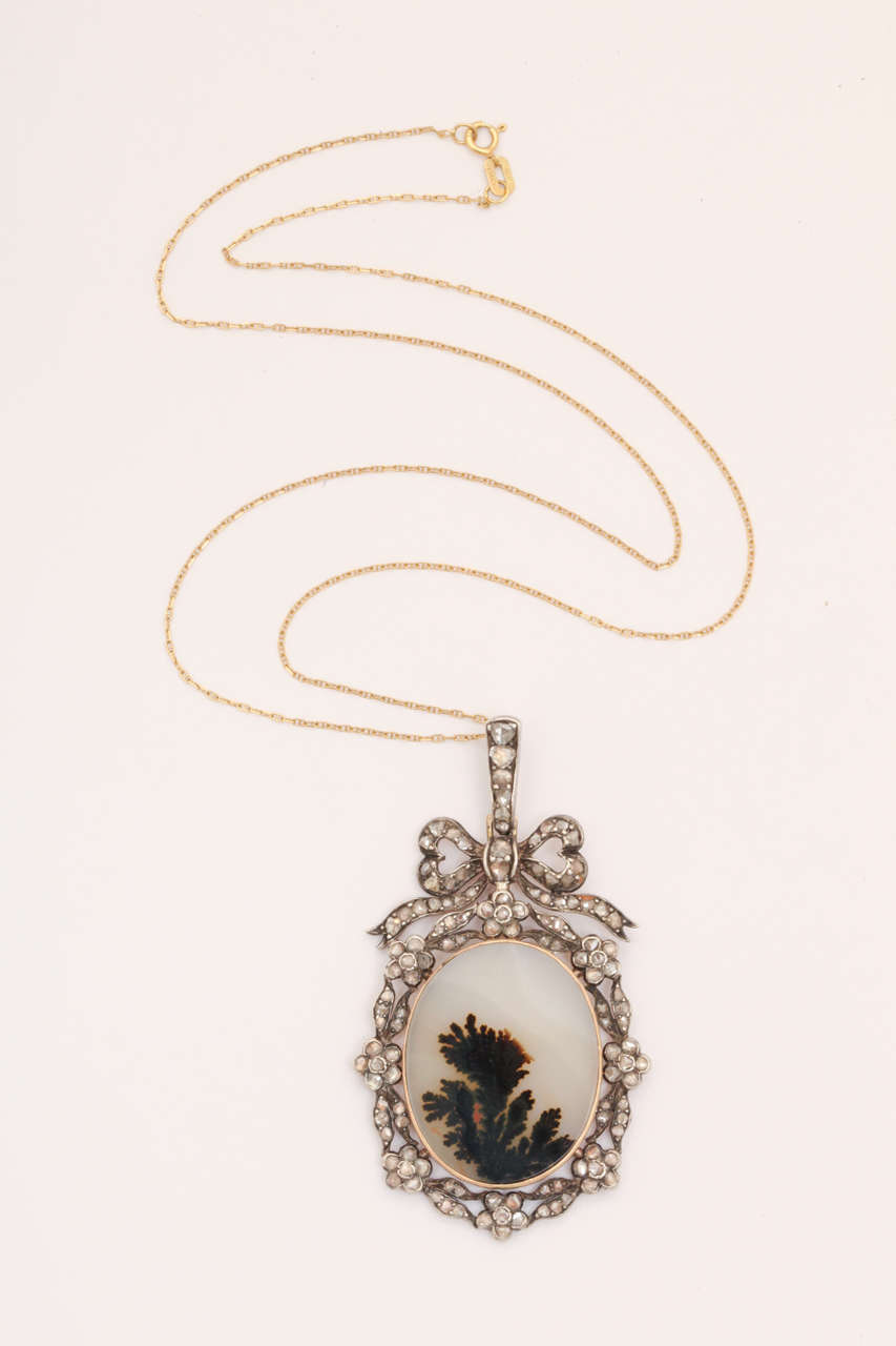 A wondrous specimen piece of agate known as moss agate exhibits the likeness of a tree top. The stone was chosen for its natural pattern and cut then smoothly polished to an oval  with sensitivity.  It is the opaque color of the moon.  Set in a