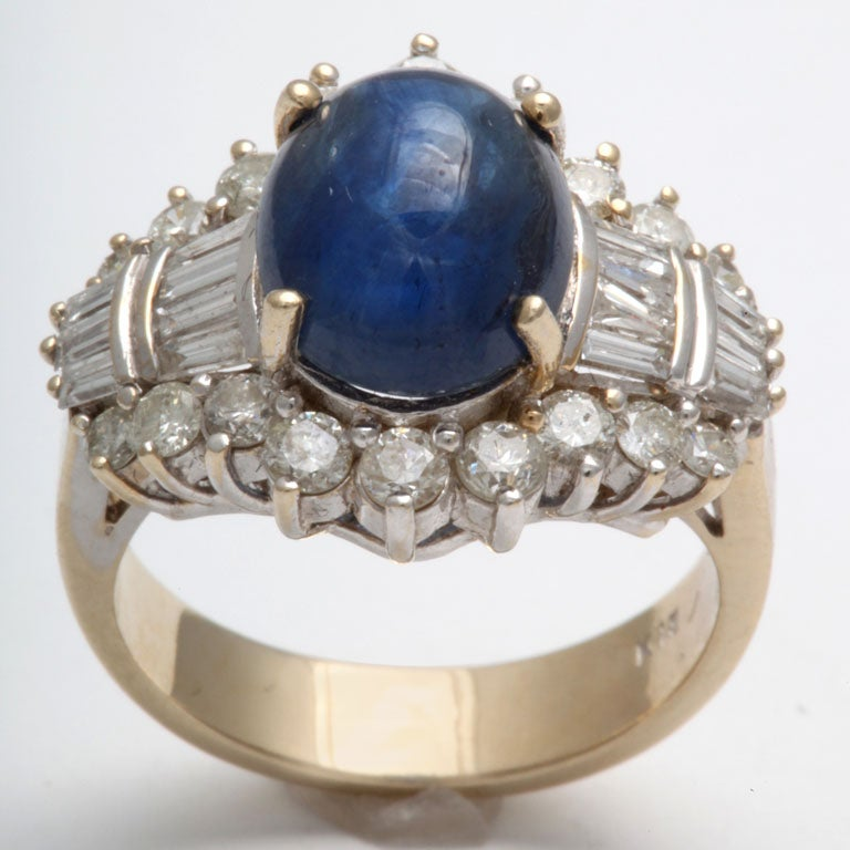 Center Cabochon Sapphire- prong set - surrounded by full clean & white Diamonds I flanked on either side by rows of Diamond Baguettes.  Shank is Yellow Gold.  Top is White Gold. Size 7.
