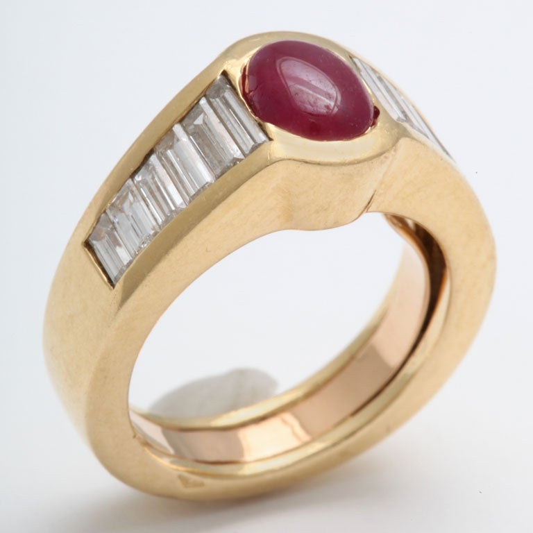 Chic Ruby & Diamond Pinky Ring.  Heavy mounting with squared profile set with rich Oval Cabochon Ruby & complemented by 6 ultra white & clean Diamond Baguettes on either side.  Has removable inner gold guard.  Size 4 1/2