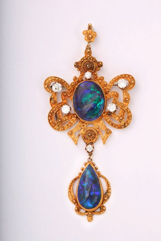 "Very Fine 1950's Etruscan  Revival Australian Black Opal Diamond Brooch / Pendant featuring an open frame stylized knotted bow design centrally set with two black opals exhibiting a very fine ""peacock"" blue & green play of color and excellent deep"