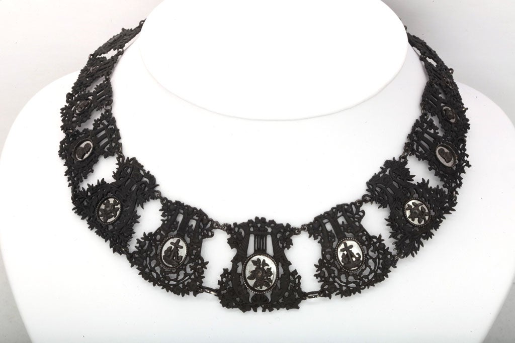 Forged in the 1800's and like a ruffle, the rare Berlin Iron Lyre necklace is a dramatic and historic display with each link set with a small cameos of iron backed with mirrored steel including anchors for loyalty, roses, birds with forget me nots,