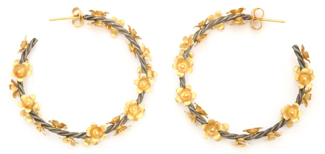A pair of rhodium plated sterling silver twisted vine hoop earrings with scattered 18kt yellow gold flowers. Width 1.50 inches