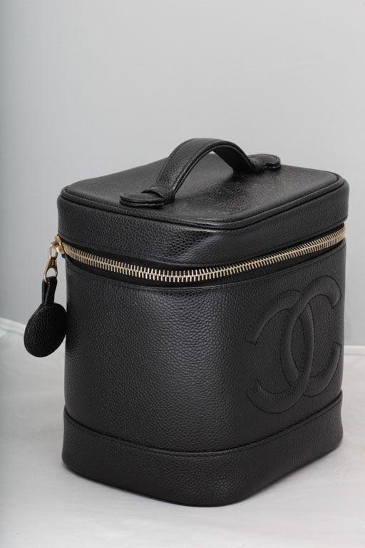 Chanel black caviar skin vanity bag with zipper closure.
