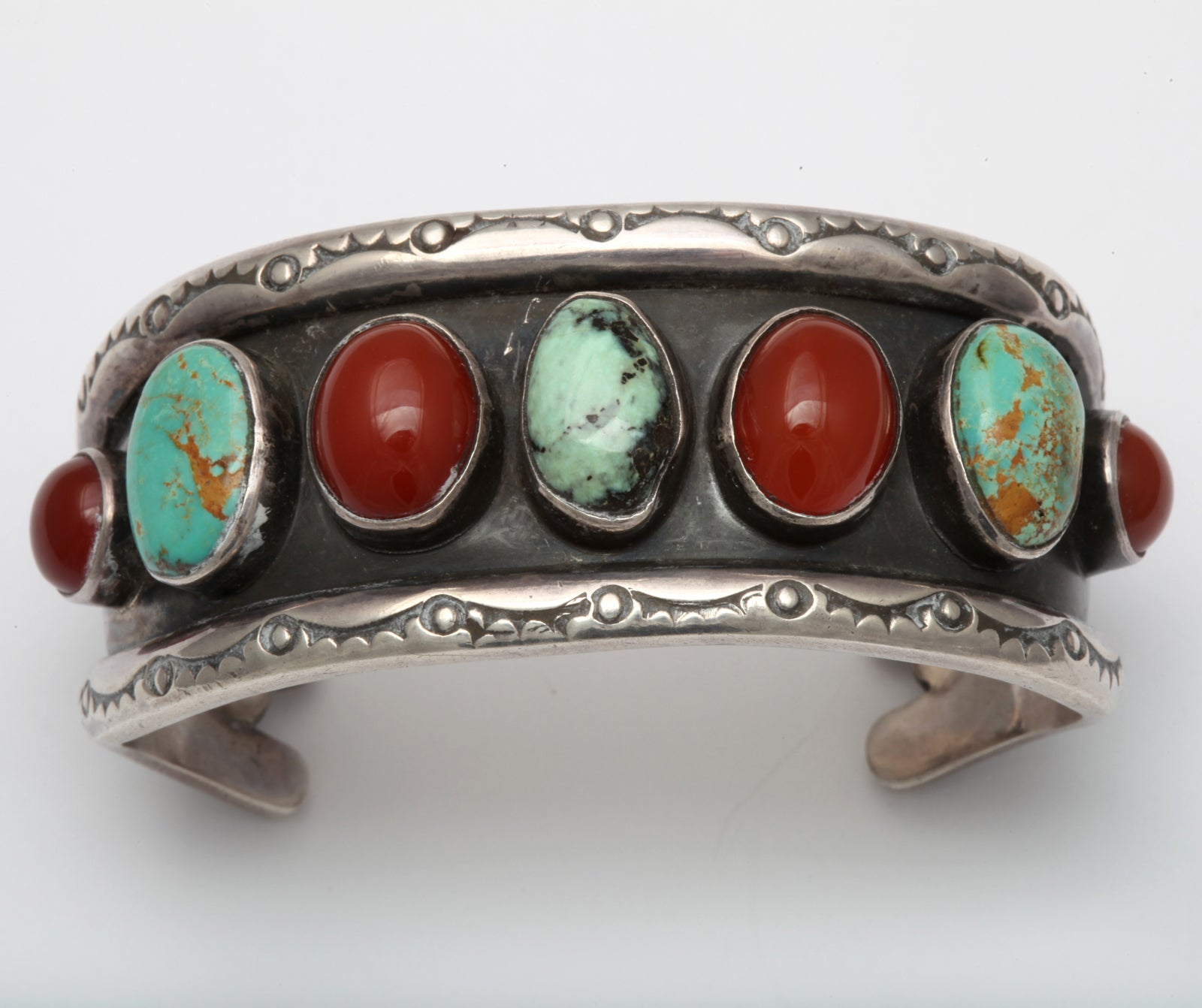 The colors of matrix turquoise and carnelian are a warm and beautiful combination in this hand made Native American cuff from Santa Fe. The stones stand out from their anodized silver background made more dramatic by the natural sterling borders.