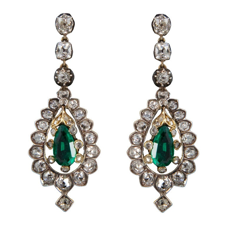 Each earring is backed in 15 karat gold, topped in silver and centers 1 pear-shaped emerald in a six-prong, diamond-set mount surrounded by diamonds in modified scallop mountings, suspended by 3 diamonds in crimped-collet mountings and completed by