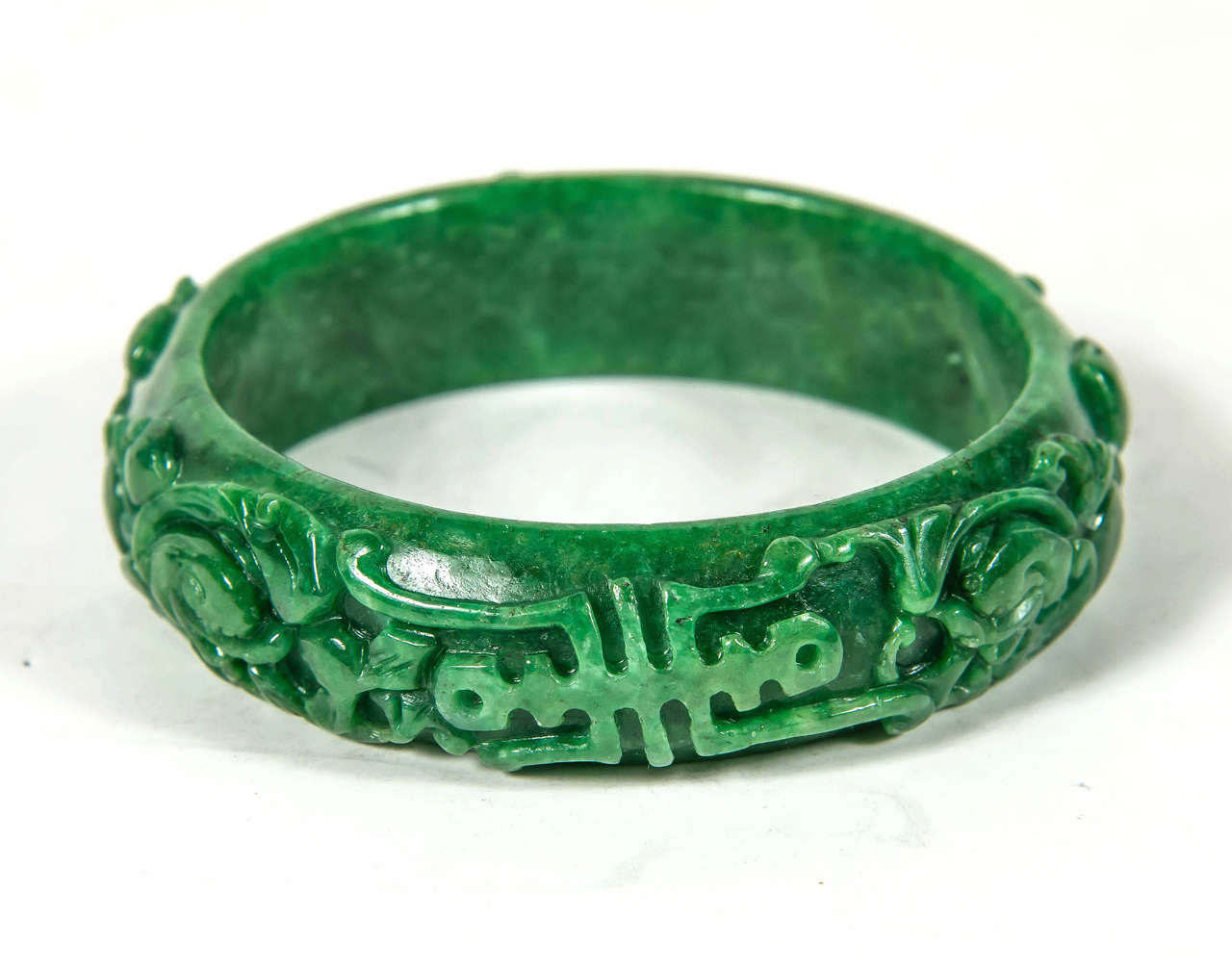 This hand carved Chinese Stone  bracelet feature a stylized floral and scroll design executed in fine hand carved jade.