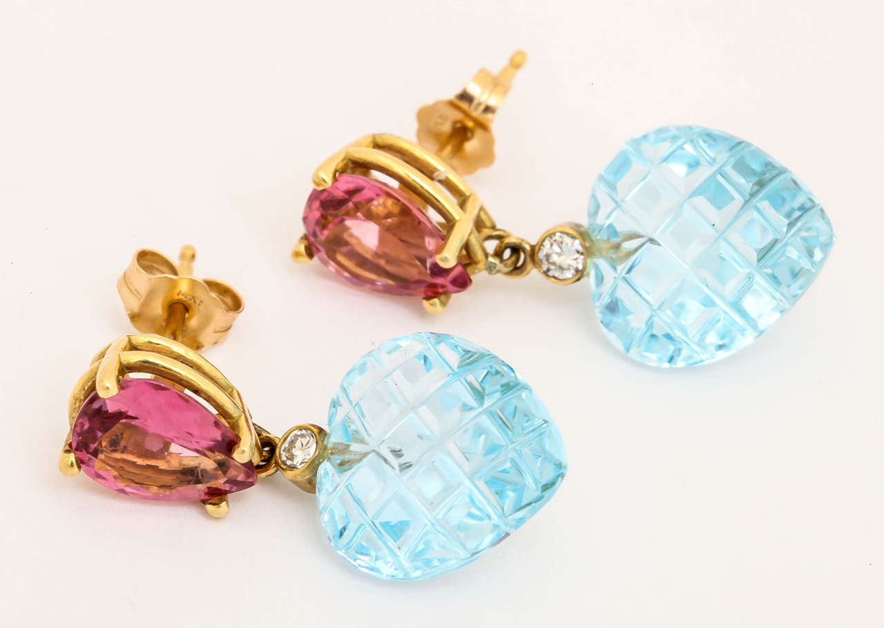 The pear shaped pink tourmalines are a wonderful bright pink and they are 8mm by 10mm. Dangling from the tourmalines is a bezel set 5 pt diamond and then  uniquely checkerboard cut blue topaz. The color combination is delicious and a great idea for