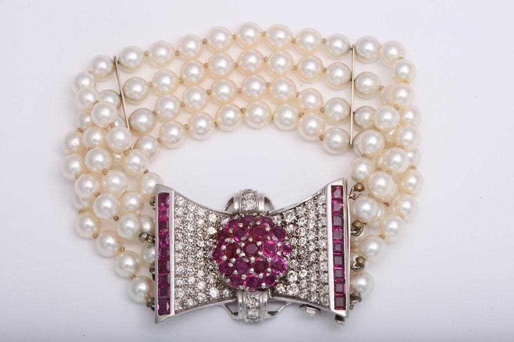 Elegant diamond and ruby bow clasp highlighted by four rows of cultured pearls.  2.75 carats approximate diamond weight.