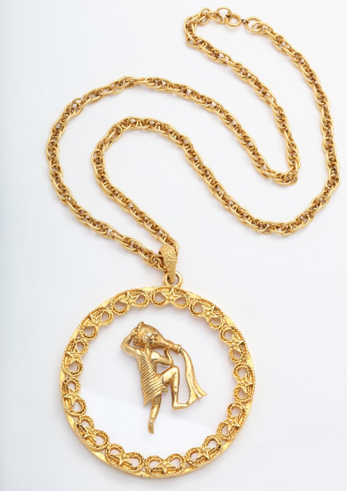 "Gold tone metal and lucite Aquarius medallion necklace. Chain is 22"" long."