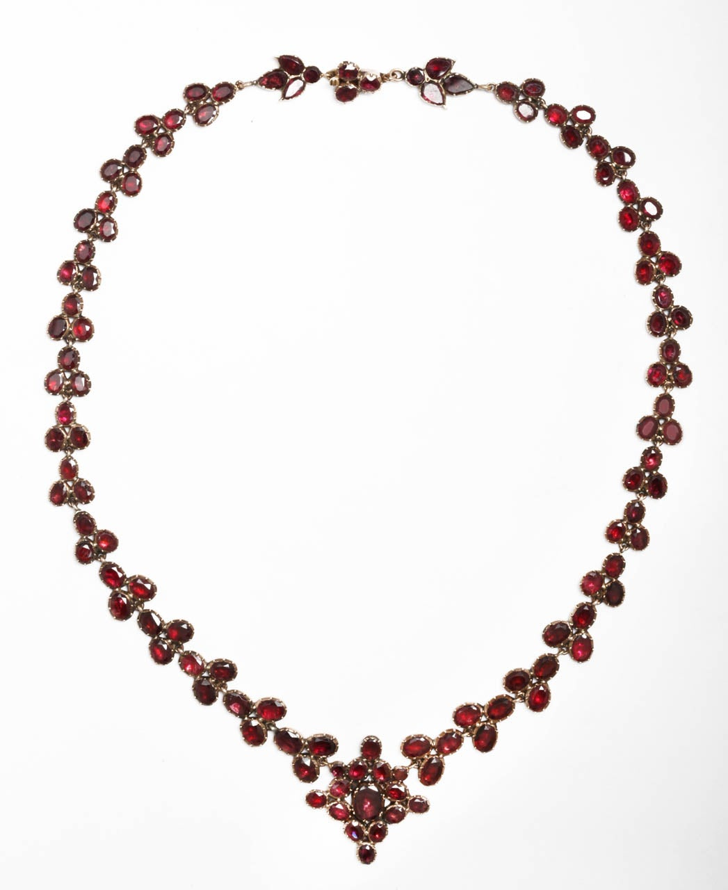 The rich red color of these foiled garnets is perfect and lustrous and must be seen to be appreciated. Photographs, with their flat image, cannot do justice to a fine antique jewel in perfect condition. Elongated posies extend from a central flower