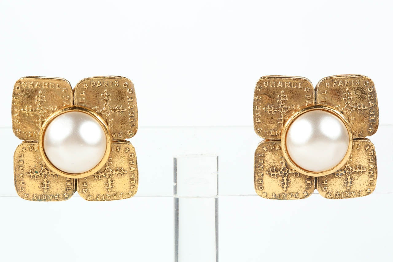 """An elegant pair of ear clips by Chanel with a dimpled poured glass pearl set atop four panels of gilt metal with the words """"Chanel"""" and """"Paris and a decorative cross in relief. Marked on the back with the """"Chanel Made in France"""" oval cartouche"""